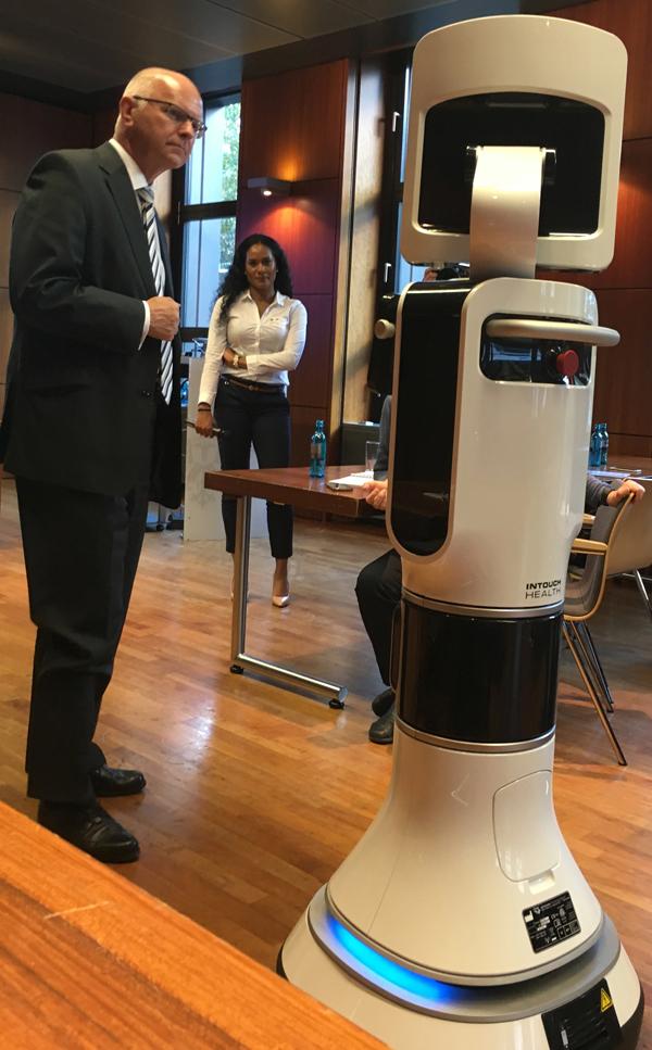 Detlef H. Franke und Gabenaa Wirke lauschen dem iRobot